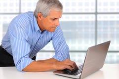 年龄生意人服务台膝上型计算机倾斜&# 图库摄影