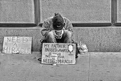 21 05 2016年 在华尔街储蓄Excange大厦前面的无家可归的穷人在曼哈顿,纽约,美国要求帮助和金钱 免版税库存图片