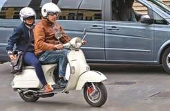 02 05 2016年 在老葡萄酒白色大黄蜂类摩托车的一对夫妇在城市交通中间在街市帕多瓦,意大利 库存图片