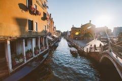 2013年7月22日在运河的威尼斯意大利美丽如画的日落有在老五颜六色的房子中的小船的向街道扔石头 免版税库存照片