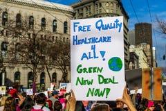 2019年1月19日旧金山/加州/美国-妇女的3月自由医疗保健和绿色罗斯福新政标志 库存照片