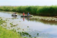 2018年6月11日,加里宁格勒地区,俄罗斯,小船的人,小船横渡的旅客,穿过有自行车的河 库存图片