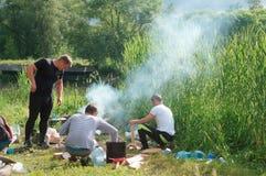 2018年6月12日,加里宁格勒地区,俄罗斯,湖的营火旅客,游人烹调在营火 免版税库存照片