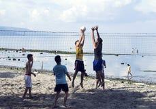 2017年8月05日,朗芒芽地,菲律宾:打沙滩排球的年轻男孩由海 免版税库存图片