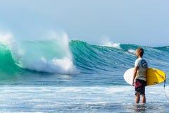 2014年8月26日:巴厘岛,印度尼西亚 打破与在等待的礁石的人身分的好的波浪用浆划  免版税库存图片