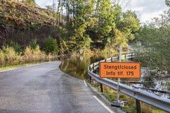 2017年10月3日:显示闭合的路的标志 在路的水 充斥从河Tovdalselva在克里斯蒂安桑 免版税库存照片