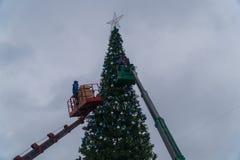 2017年12月15日 俄国 市多莫杰多沃 拉什哈巴德中央广场 工作者垂悬在大都市圣诞节的欢乐球 免版税库存照片
