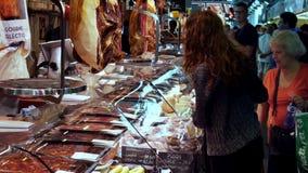 2017年9月22日-巴塞罗那,西班牙,墨卡托de la Boqueria食品批发市场:有产品名单的妇女是在 股票视频