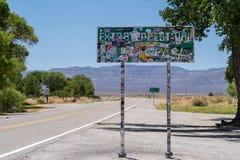 2018年7月4日-拉结,内华达:地球外的高速公路的地标标志在从游人探索的贴纸报道 免版税库存图片