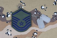 2018年5月12日 美国空军队军士长茂盛的补丁和卡箍标记在沙漠伪装制服背景 免版税库存图片