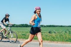 2018年5月26-27,Naliboki,白俄罗斯全白俄罗斯语非职业马拉松Naliboki A妇女沿着路的一个骑自行车者跑 免版税库存图片