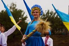 2017年8月28日:有麦子耳朵的秋天女孩在有一个花圈的一件弯曲的蓝色礼服在她的头在乌克兰假日在英国举行了 免版税库存图片
