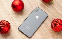 2017年11月 iPhone 10在桌上说谎在圣诞节球旁边 免版税库存图片