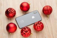 2017年11月 iPhone 10在桌上说谎在圣诞节球旁边 免版税库存照片