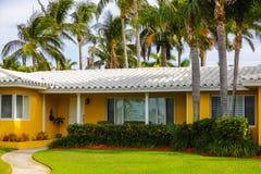 1950年` s佛罗里达家绘了与绿草和棕榈tre的黄色 图库摄影