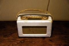 1950年` s收音机,白色在木桌&镶边墙纸上 库存照片