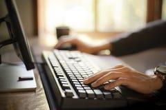 并且工作坐计算机,喝咖啡早晨 免版税库存图片