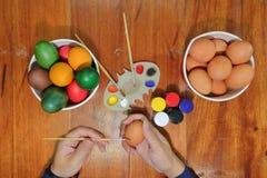 年轻幸福人的手顶视图绘与一把油漆刷的鸡蛋在准备的愉快的复活节天木桌上 库存图片