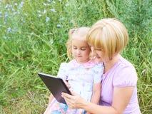 幸福冲浪使用片剂的妈妈和女儿网户外  免版税图库摄影