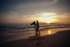 幸福和爱夫妇浪漫场面在日落成为伙伴在海滩 爱 享用 愉快 免版税库存图片