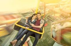 幸福在弗累斯大转轮的夫妇骑马 免版税库存图片