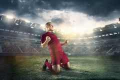 幸福在目标以后的足球运动员在体育场的领域 库存照片