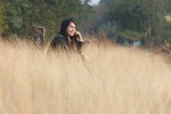 幸福妇女享用在草原坐 免版税图库摄影