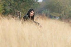 幸福妇女享用在草原坐 免版税库存图片