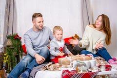 幸福家庭、父亲、母亲和儿子,早晨在为圣诞节装饰的卧室 他们打开礼物并且获得乐趣 新年度 图库摄影