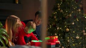 幸福家庭为圣诞节庆祝做准备:母亲、谈话的父亲和的孩子微笑和,当开放礼物在家时 股票录像
