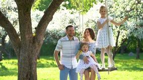 幸福家庭人亲吻妇女的和他们的女孩在春季庭院里摇摆 股票录像
