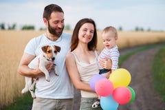 幸福家庭和狗一起享受室外时间 库存图片