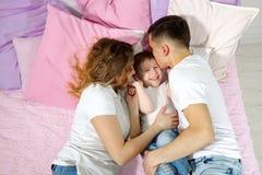 幸福家庭在床上,妈妈、儿子和爸爸是一起亲吻和拥抱 免版税库存照片