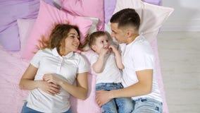 幸福家庭在床上,妈妈、儿子和爸爸是一起亲吻和拥抱 股票录像
