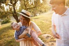 幸福家庭在庭院里走togther 母亲使用与她的儿子并且关心他在手上 r 免版税库存图片