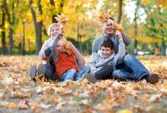 幸福家庭在秋天城市公园坐落叶 获得的孩子和的父母摆在,微笑,演奏和乐趣 明亮的黄色 库存照片