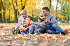 幸福家庭在秋天城市公园坐落叶 获得的孩子和的父母摆在,微笑,演奏和乐趣 明亮的黄色 图库摄影