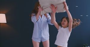 幸福家庭妈妈有保姆和小孩的女儿乐趣在床上的枕头战,年轻母亲保姆笑的使用 影视素材