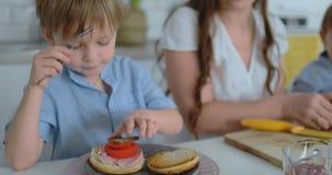 幸福家庭是一件白色礼服的一个年轻美丽的母亲有准备一个白色厨房的蓝色衬衣的两个儿子的 影视素材