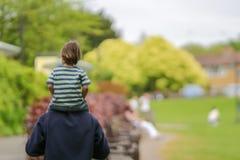 幸福家庭概念-坐父亲脖子和有乐趣在公园在好日子孩子的被弄脏的图片 免版税库存图片