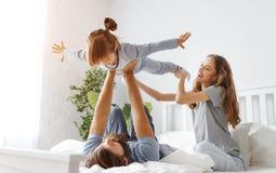 幸福家庭母亲、父亲和孩子在床上 免版税库存照片