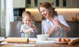 幸福家庭母亲和儿子在厨房里烘烤揉的面团 免版税库存照片