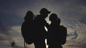 幸福家庭游人现出轮廓在日落拥抱亲吻 配合旅行概念 男人和妇女加上生活方式 股票录像