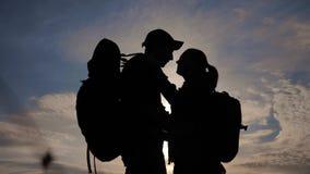 幸福家庭游人现出轮廓在日落拥抱亲吻 配合旅行概念 男人和妇女加上背包 股票视频