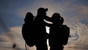 幸福家庭游人现出轮廓在日落拥抱亲吻 配合旅行概念 男人和妇女加上背包 影视素材