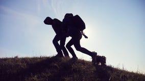 幸福家庭男人和妇女走商务旅游的配合手拉手去游人剪影在它上面山 影视素材