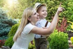 幸福家庭的生活片刻!一起使用母亲和儿子的孩子获得乐趣在草在晴朗的夏日 库存照片