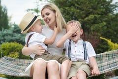 幸福家庭的生活片刻!年轻母亲和两个美丽的儿子在摇摆乘坐 免版税库存照片
