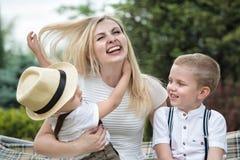 幸福家庭的生活片刻!年轻母亲和两个美丽的儿子 免版税图库摄影