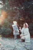 幸福家庭的画象:有她的走在冬天城市公园的小逗人喜爱的女儿的一年轻美女 免版税库存照片